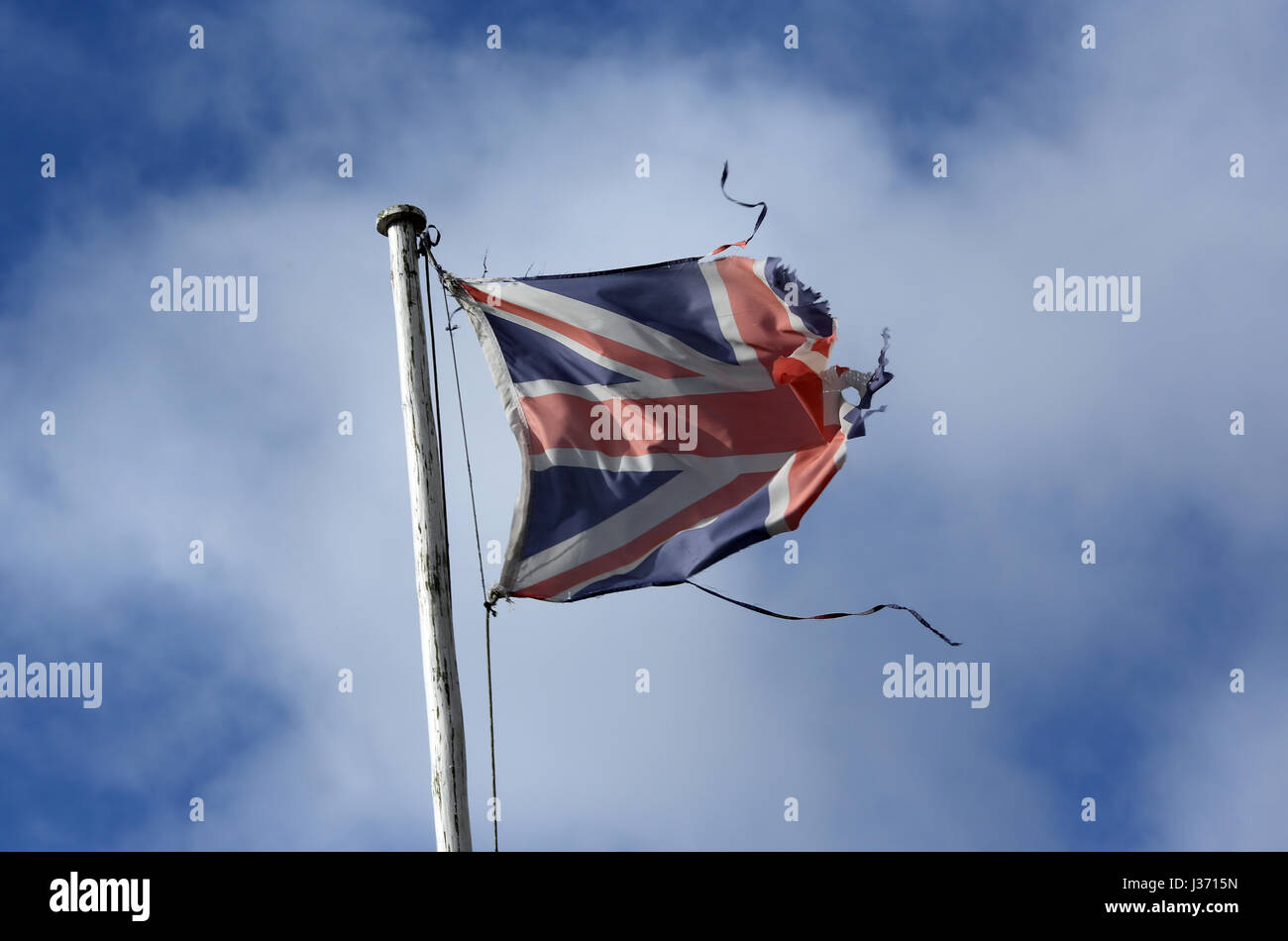 A tattered Union Flag blowing in the wind pictured against a cloudy bright blue sky of a flagpole in Ballater Scotland - Stock Image