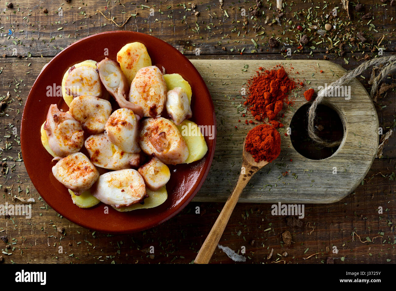 high-angle shot of an earthenware plate with pulpo a la gallega, a recipe of octopus typical in Spain served on Stock Photo