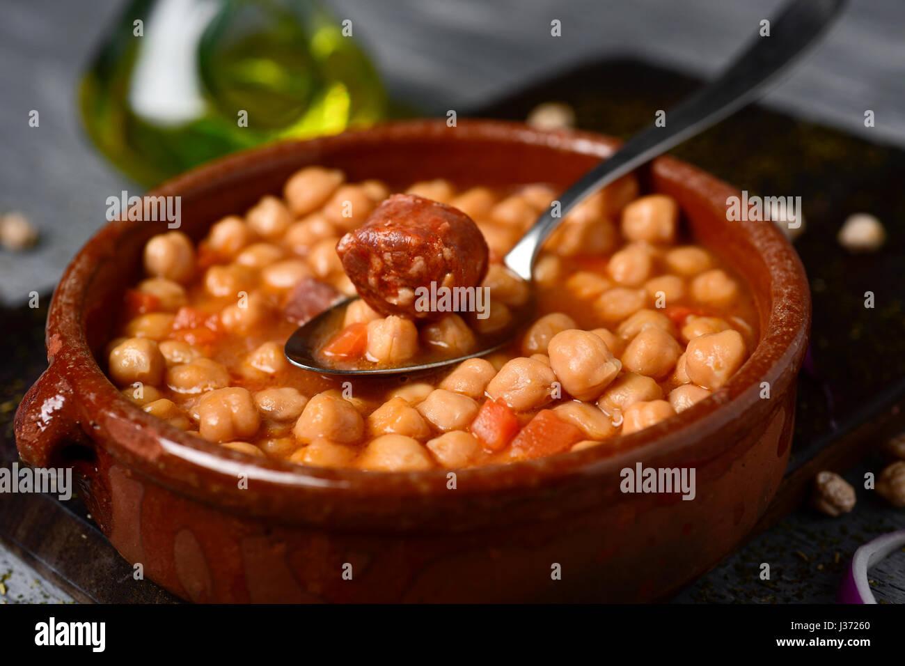 closeup of an earthenware bowl with potaje de garbanzos, a spanish chickpeas stew with chorizo and serrano ham, - Stock Image
