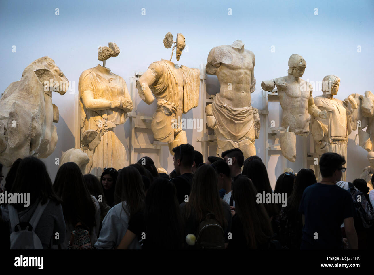 """""""The Gods look down"""", Tourists viewing sculptures from The East pediment of the Temple of Zeus. Archaeological  Stock Photo"""