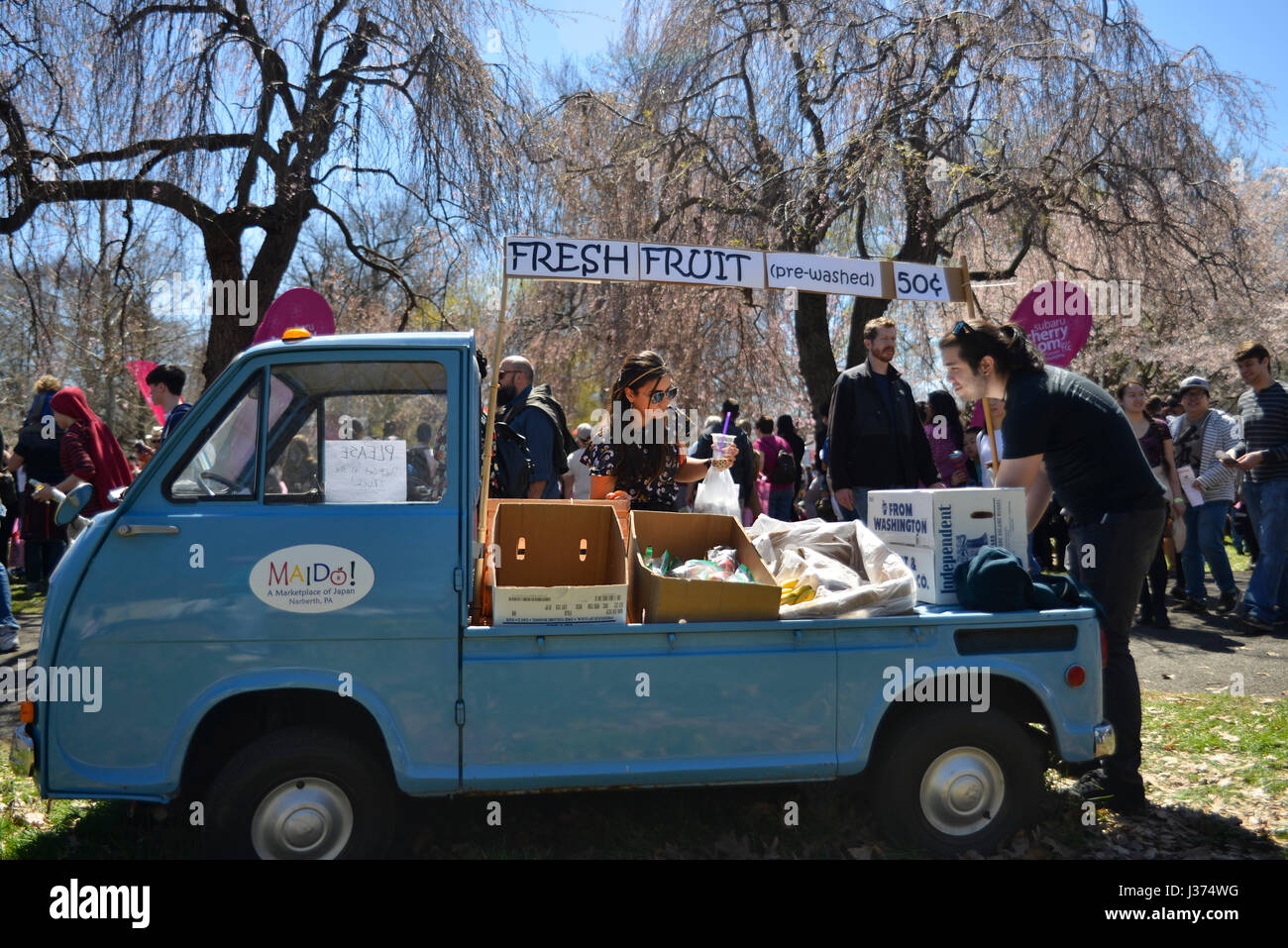 This nearly fifty-year-old tiny Japanese pick up truck serves as a fresh fruit stand as thousands enjoy iconic elements Stock Photo