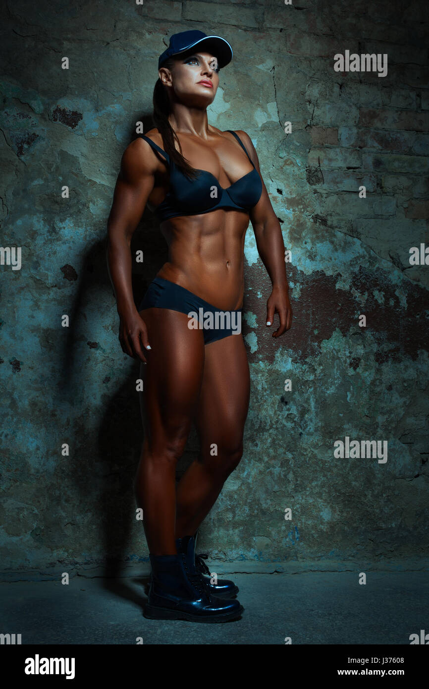Woman with big muscles posing on wall background. Stock Photo