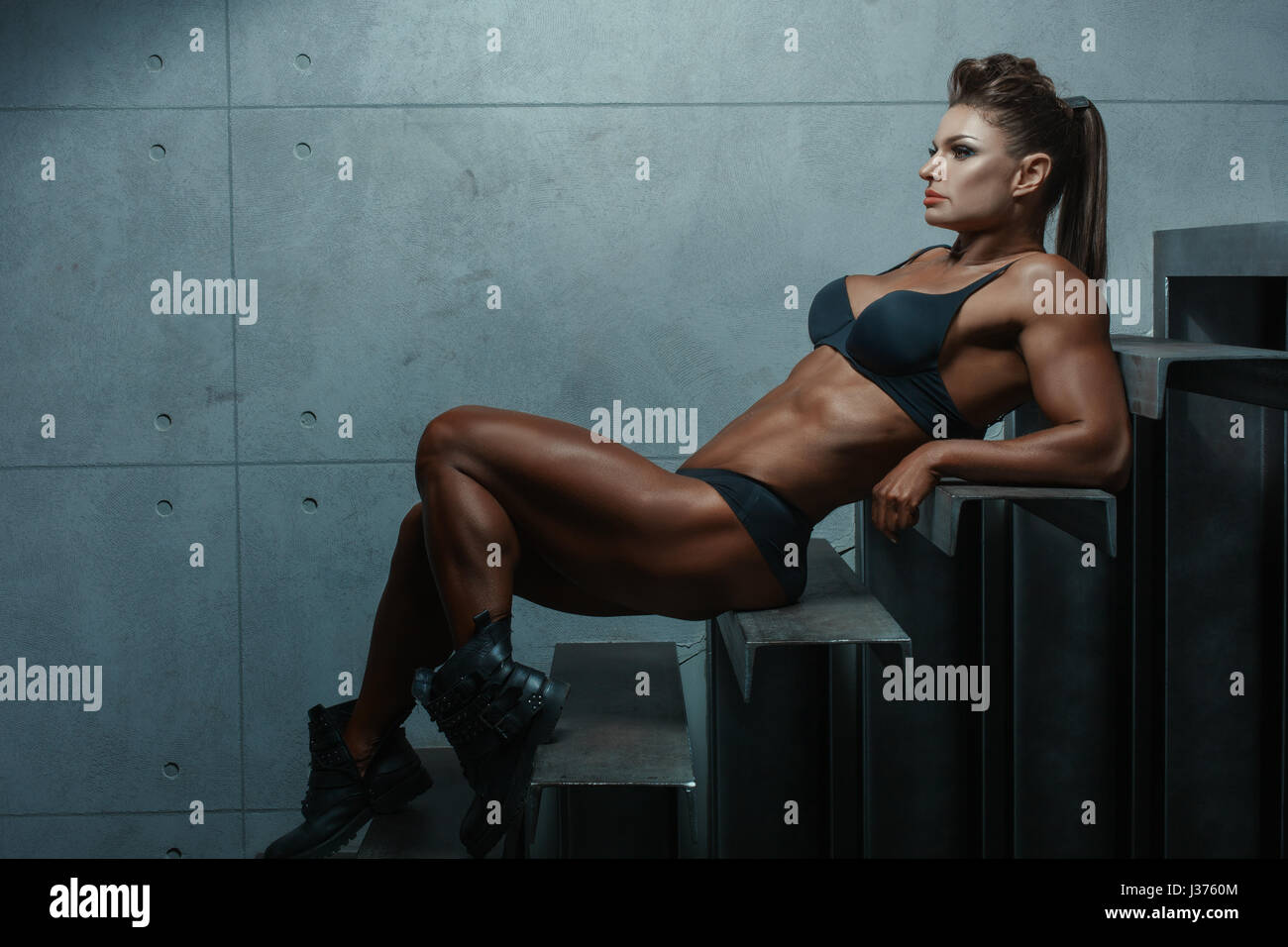 Female bodybuilder lying on the steps, her muscles are clearly visible. Stock Photo