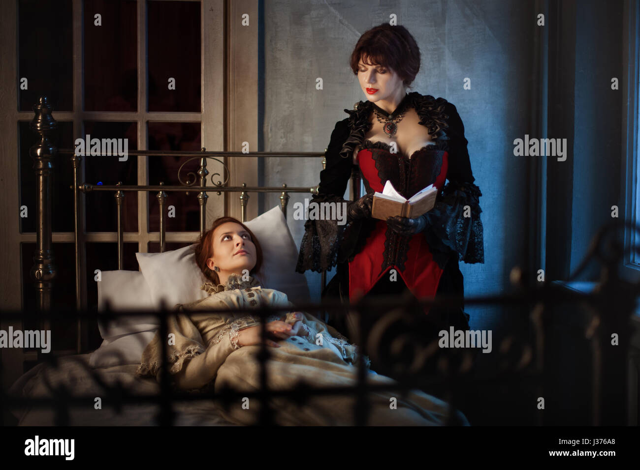 Sick woman lying on a bed next to another woman reading a book, in the Gothic style retro. - Stock Image