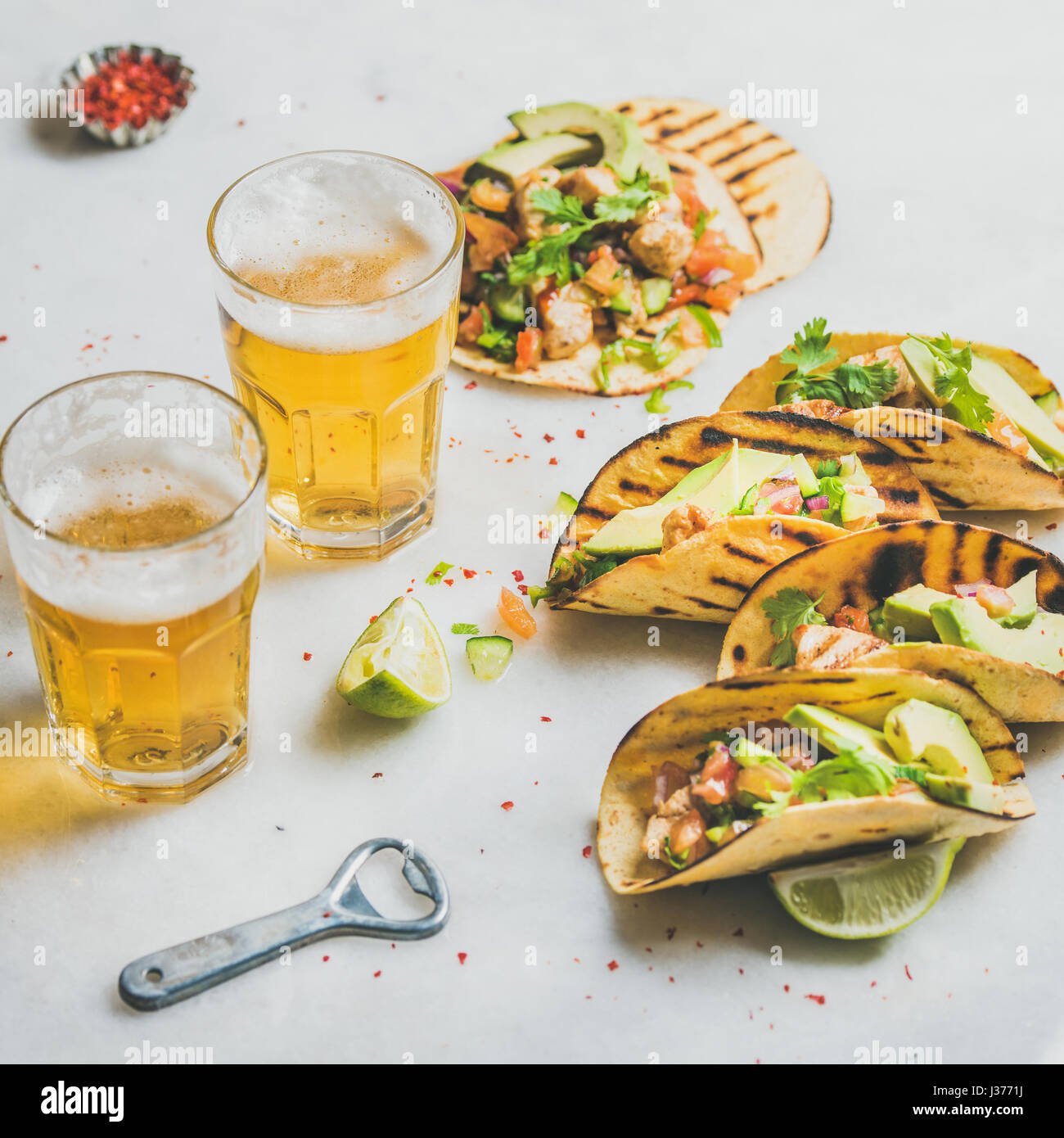 Healthy corn tortillas with beer in glasses over light background - Stock Image