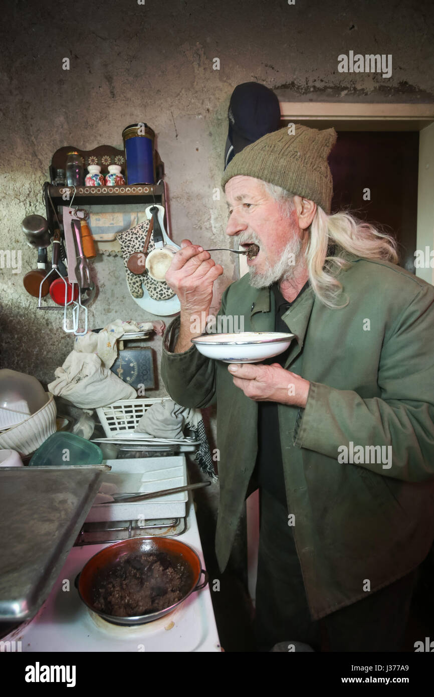 An old man cooking meat on stove and tasting the food. - Stock Image