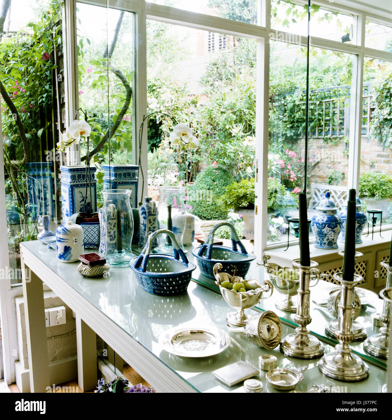 Assorted antiques on table inside conservatory. - Stock Image