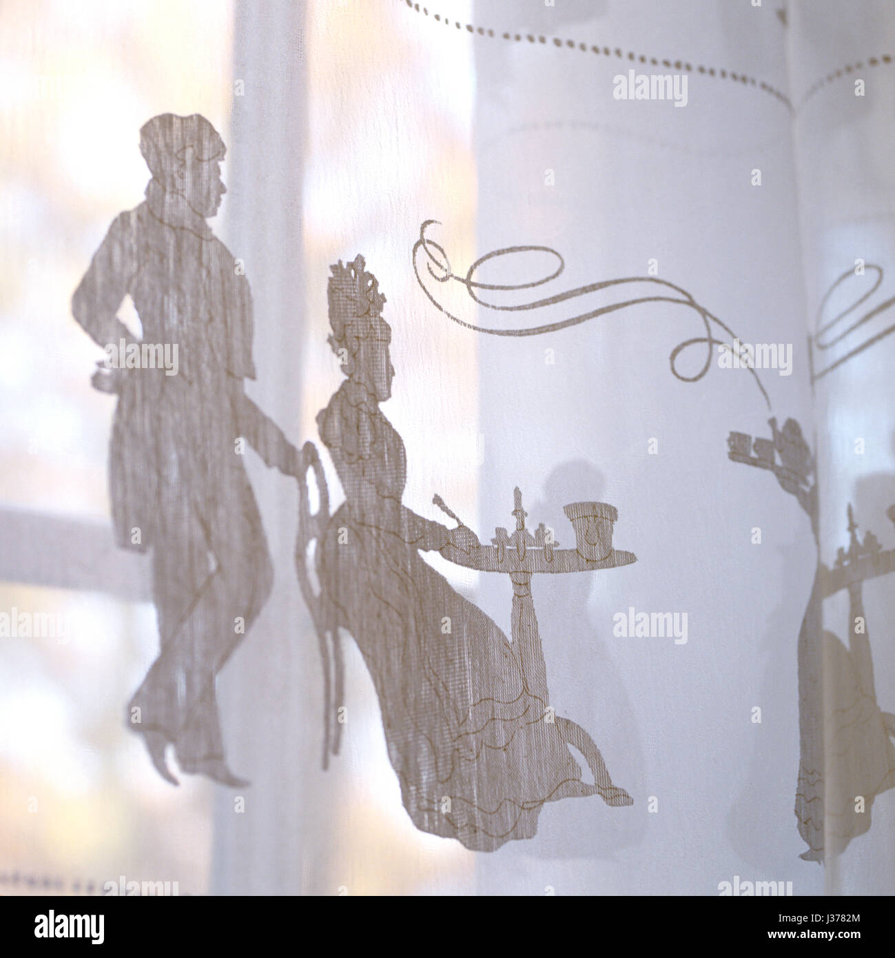 Sheer curtain with illustration of man and woman. - Stock Image