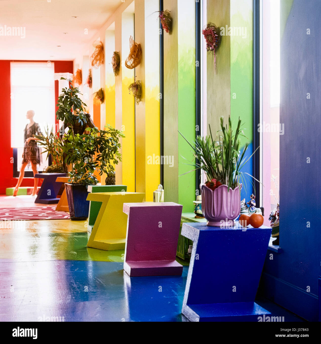 Colorful side tables with pot plants. - Stock Image