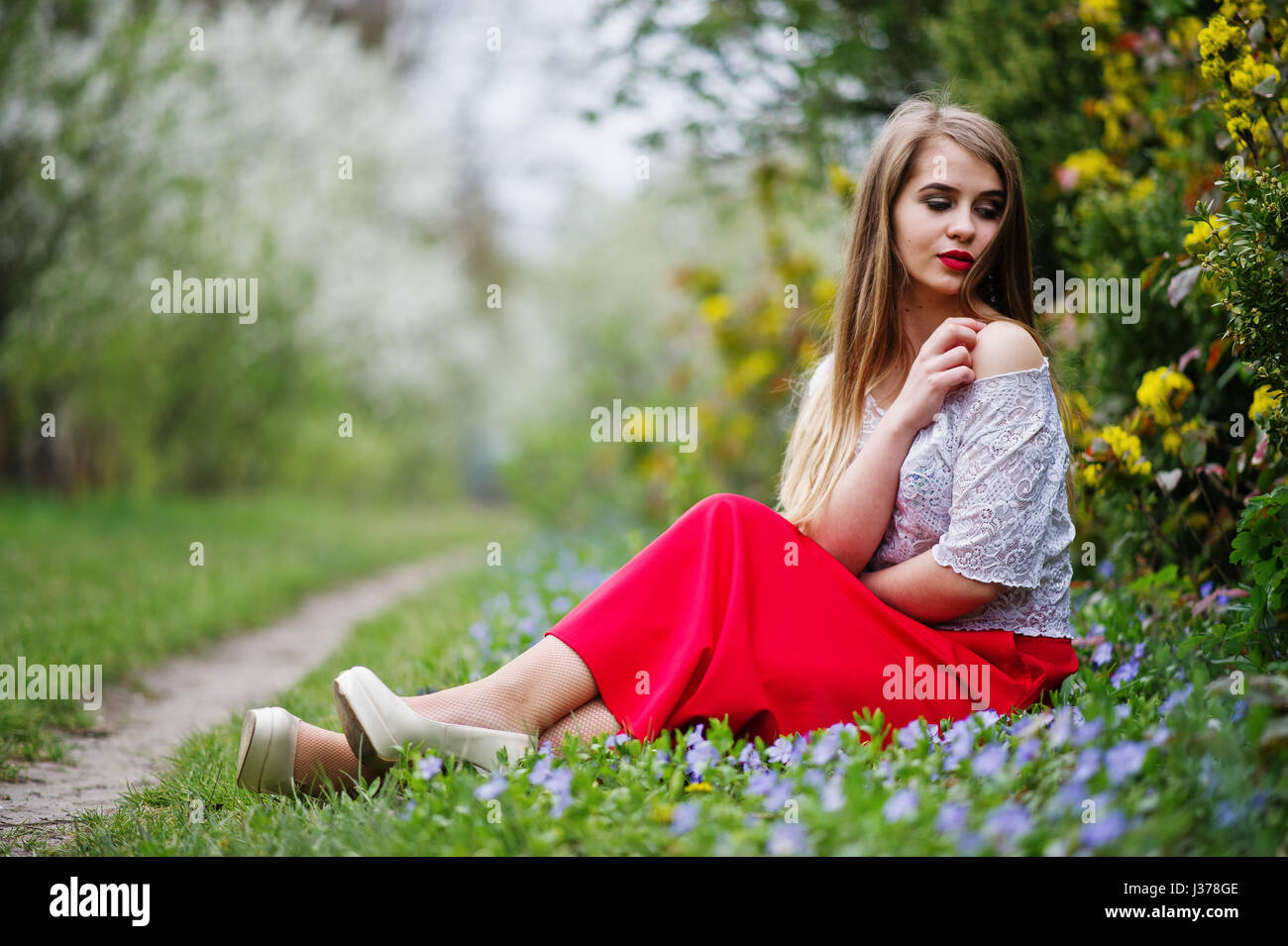 Portrait Of Sitiing Beautiful Girl With Red Lips At Spring Blossom