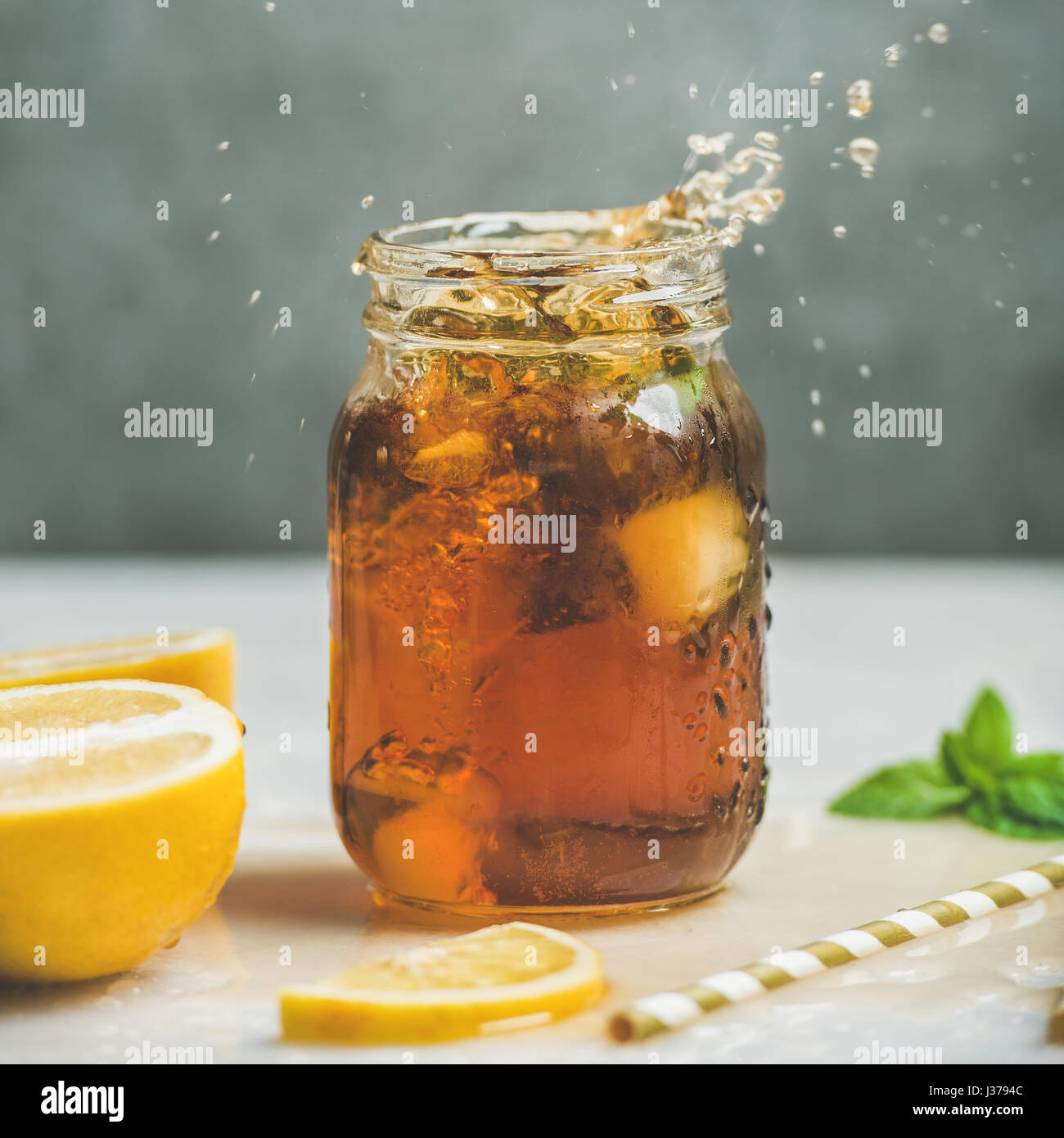 Iced tea with fresh herbs in jar with splashes - Stock Image