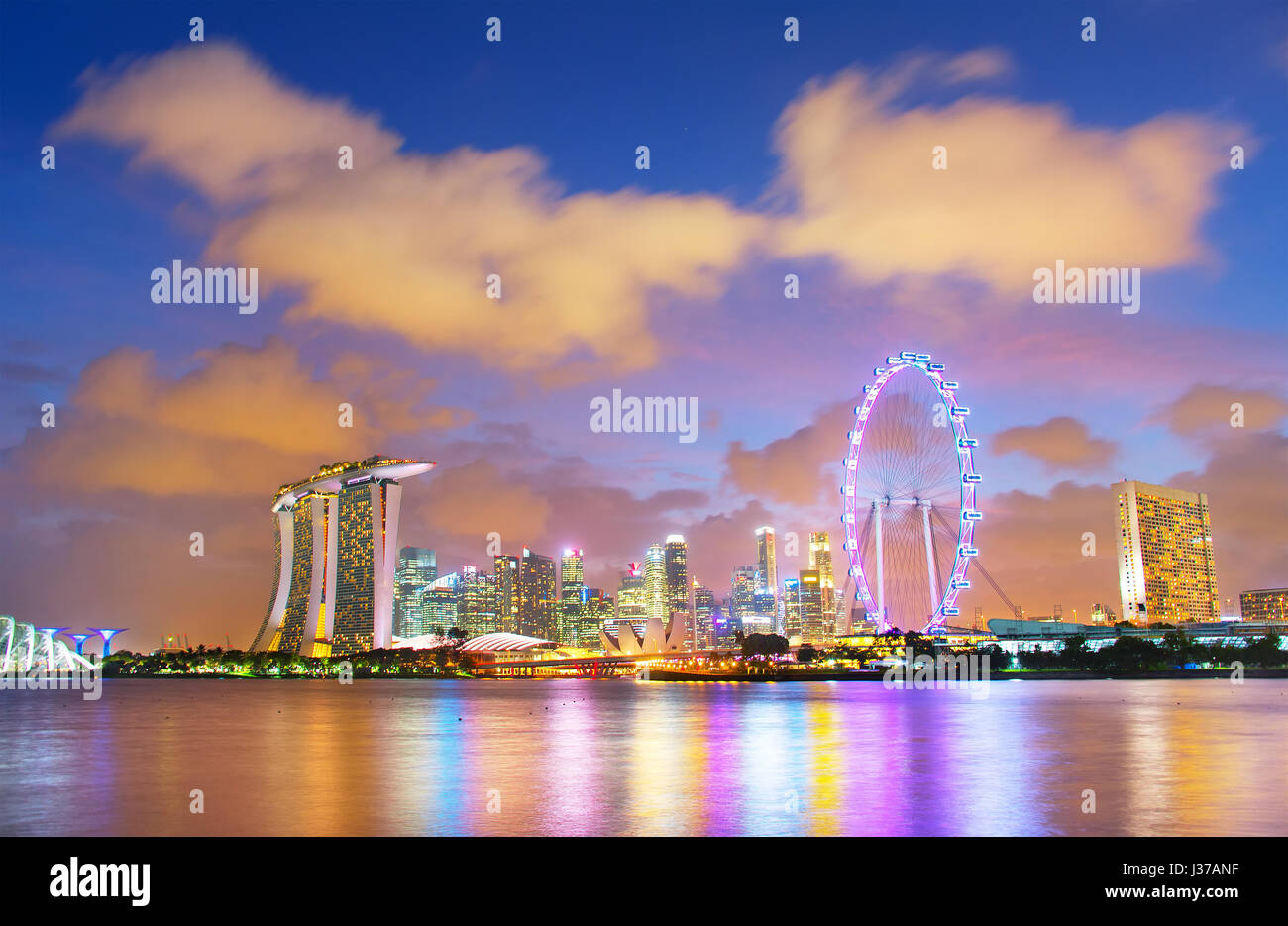 Singapore Downtown Core reflecting in Singapore river at dusk - Stock Image