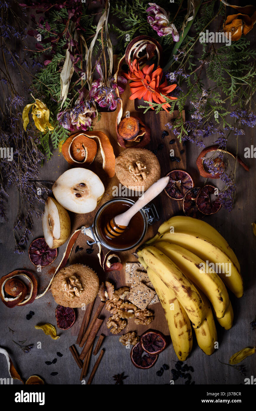 Homemade banana and nut muffins with honey and spices on wooden board decorated with flowers. Top view. - Stock Image