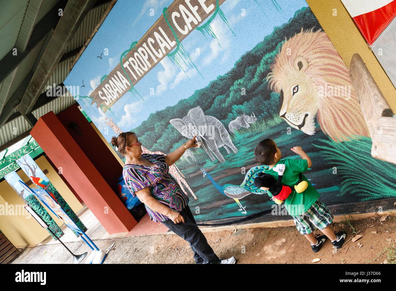 Woman and boy at mural of Sabana Tropical Cafe, Mayaguez Zoo (Juan A. Rivero), Puerto Rico - Stock Image