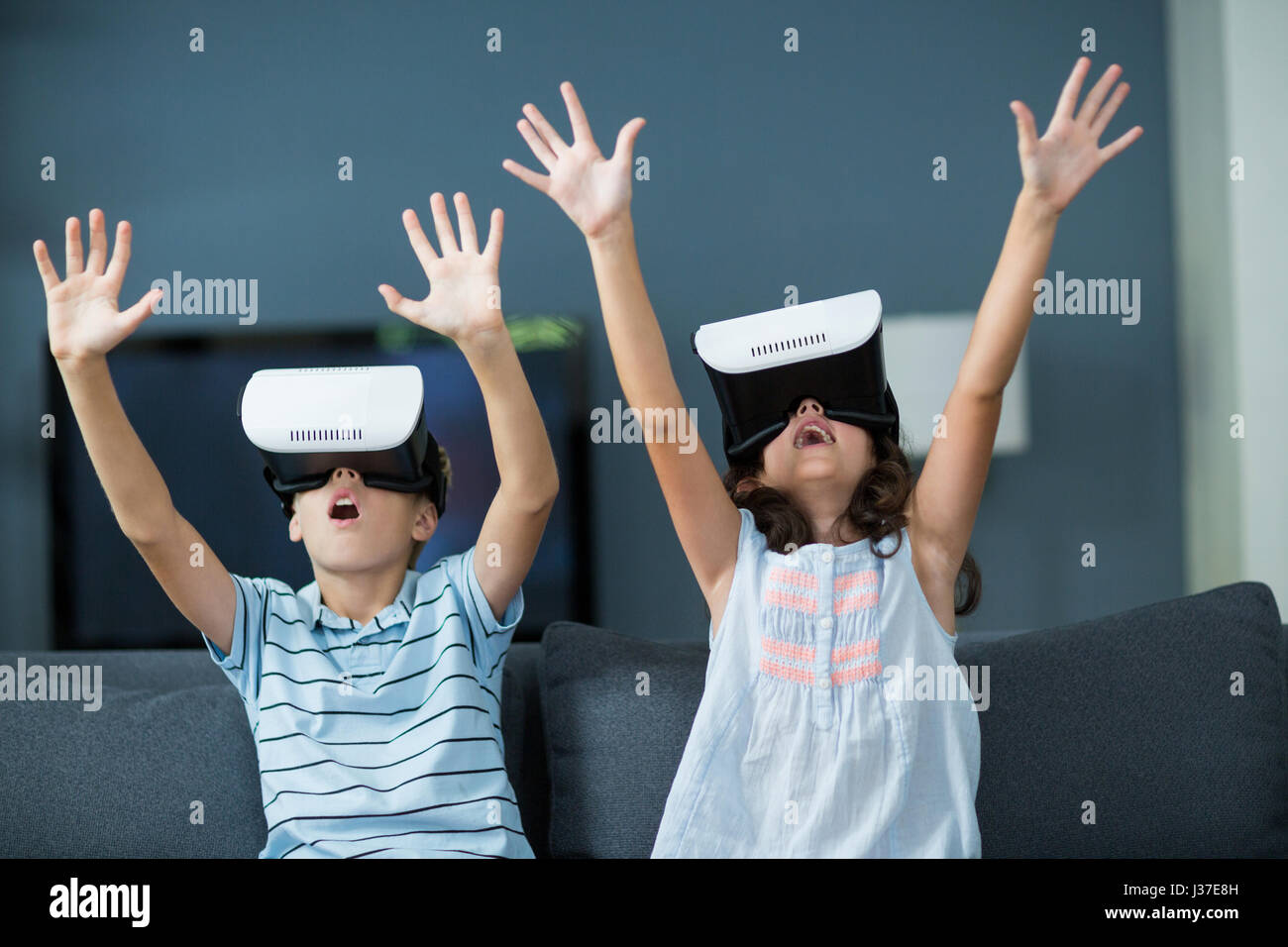 Siblings using virtual reality headset in living room at home - Stock Image