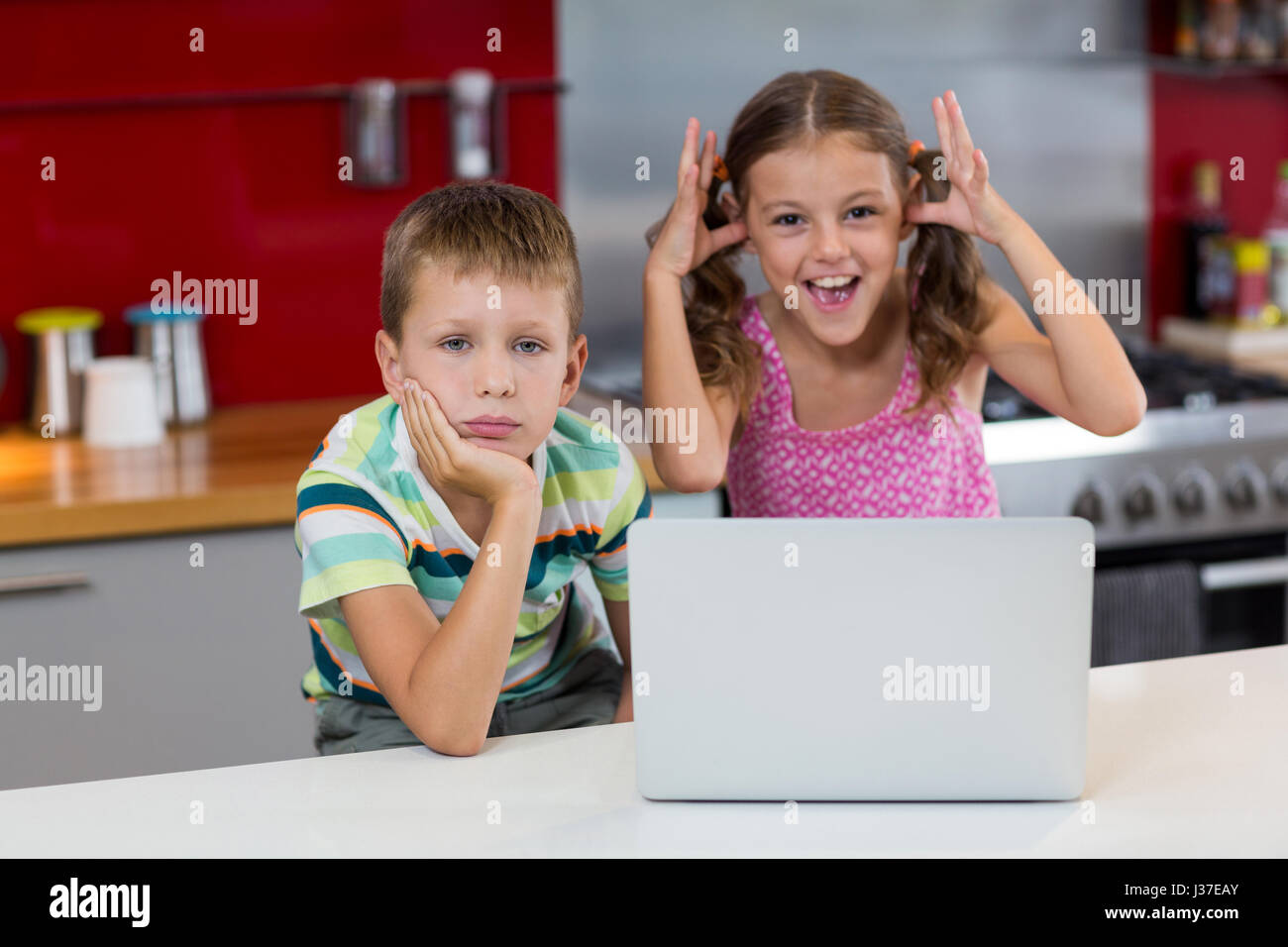 Girl teasing his brother in kitchen at home - Stock Image