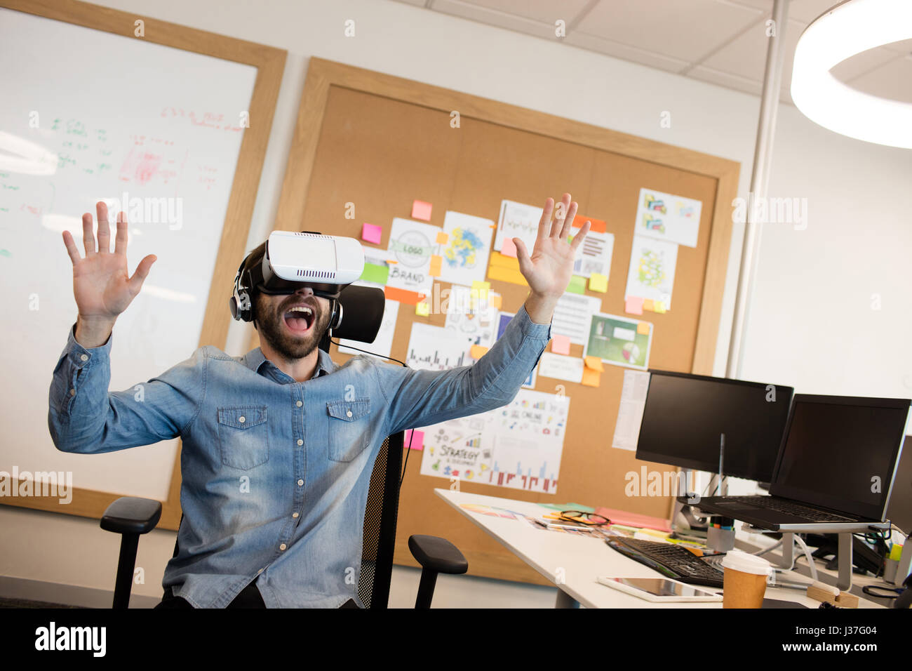 Businessman screaming while experiencing virtual reality in modern office - Stock Image
