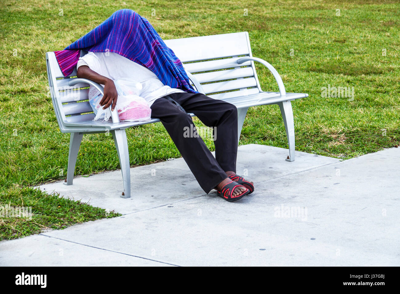 Miami Beach Florida Lummus Park park bench Black man sleeping covered face head blanket hiding mental health illness - Stock Image