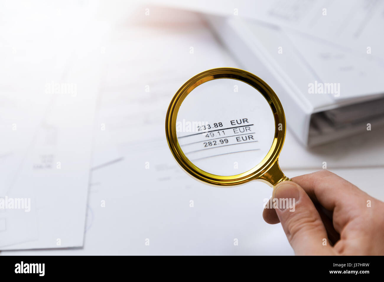 audit concept - auditor checking bills with magnifying glass - Stock Image