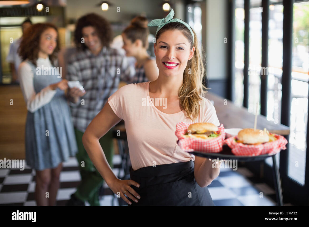 Portrait of smiling young waitress serving burger with customers in background at restaurant - Stock Image