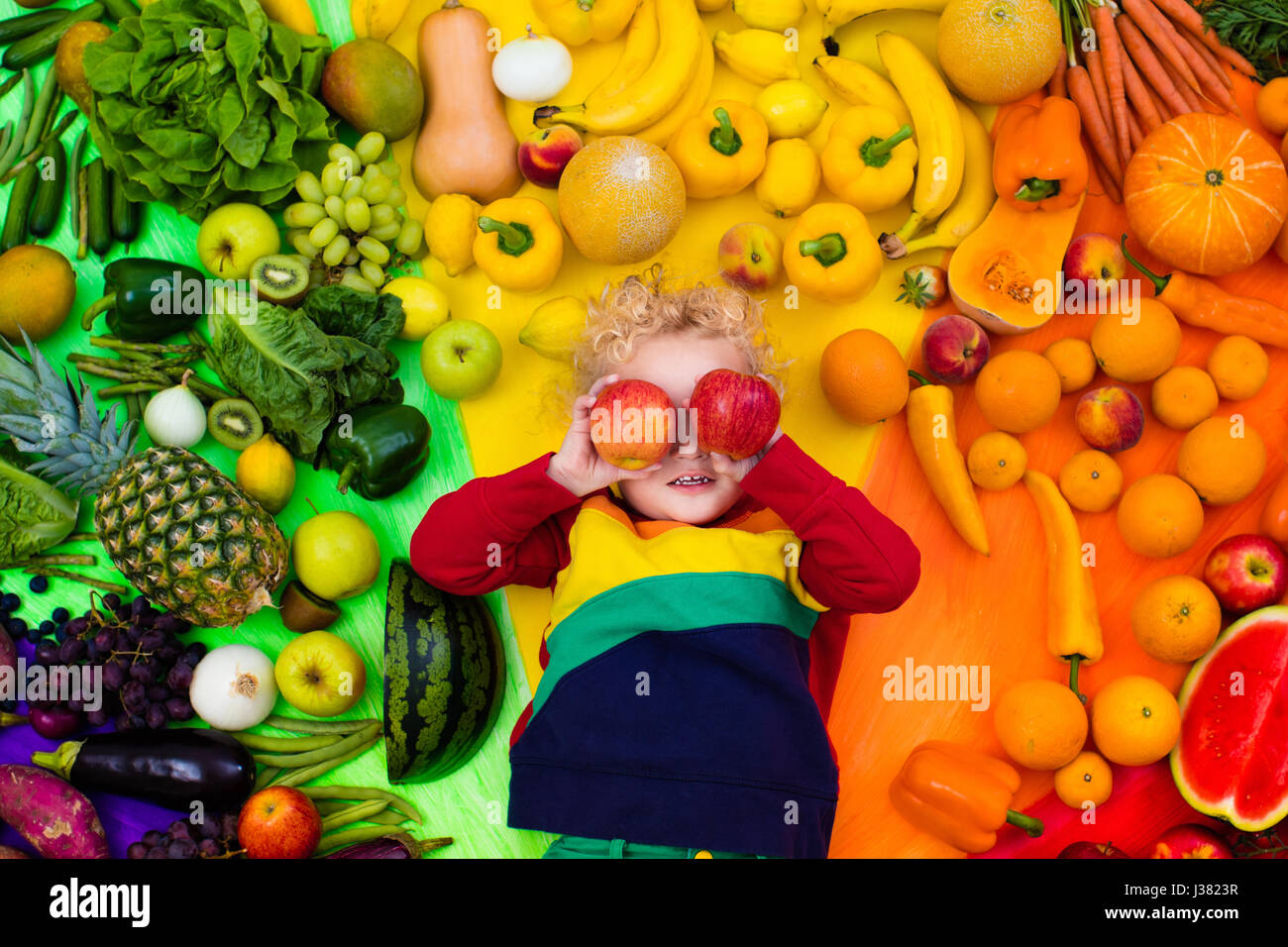 Baby boy with variety of fruit and vegetable. Colorful rainbow of raw fresh fruits and vegetables. Child eating - Stock Image