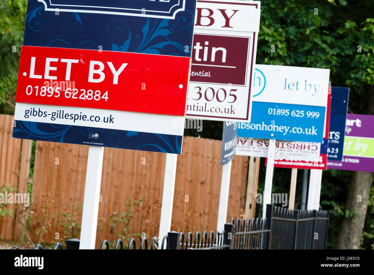 Estate agent 'let by' signs advertise property in a suburb of London - Stock Image