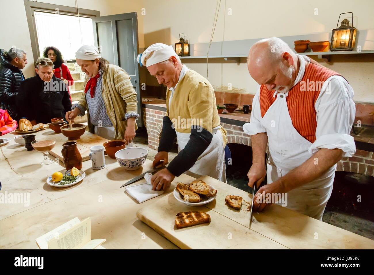 Chefs in traditional costume cooking in the Royal Kitchens, Kew Gardens, London, UK - Stock Image