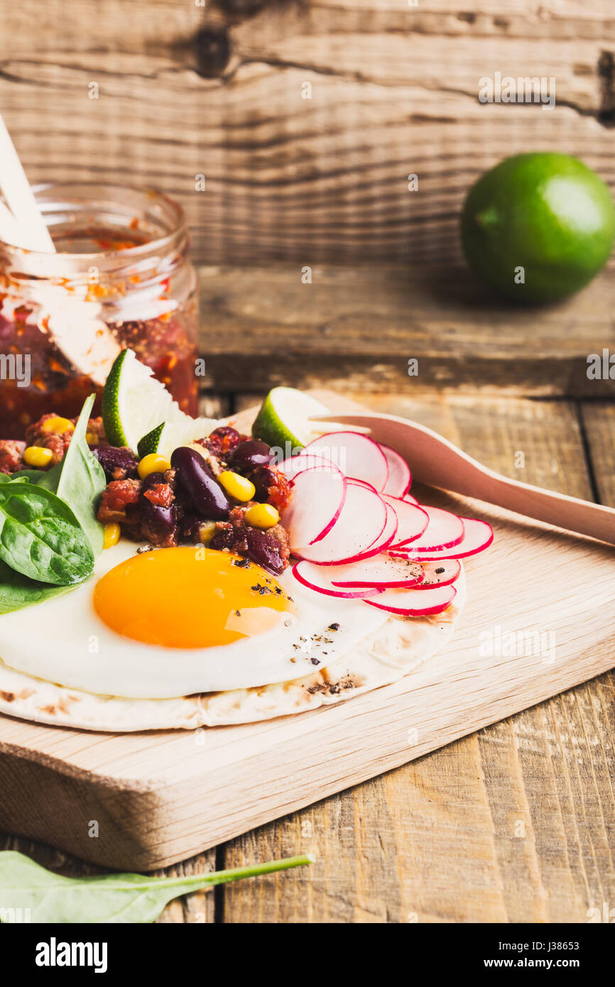 Fried egg tacos with chili con carne on rustic cutting board, Mexican traditional food Stock Photo