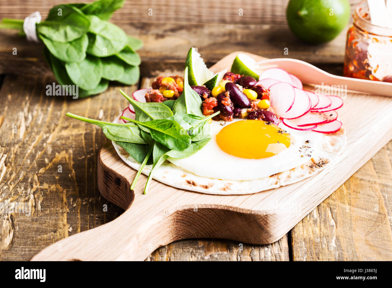 Fried egg tacos with chili con carne on rustic cutting board, Mexican traditional food - Stock Image