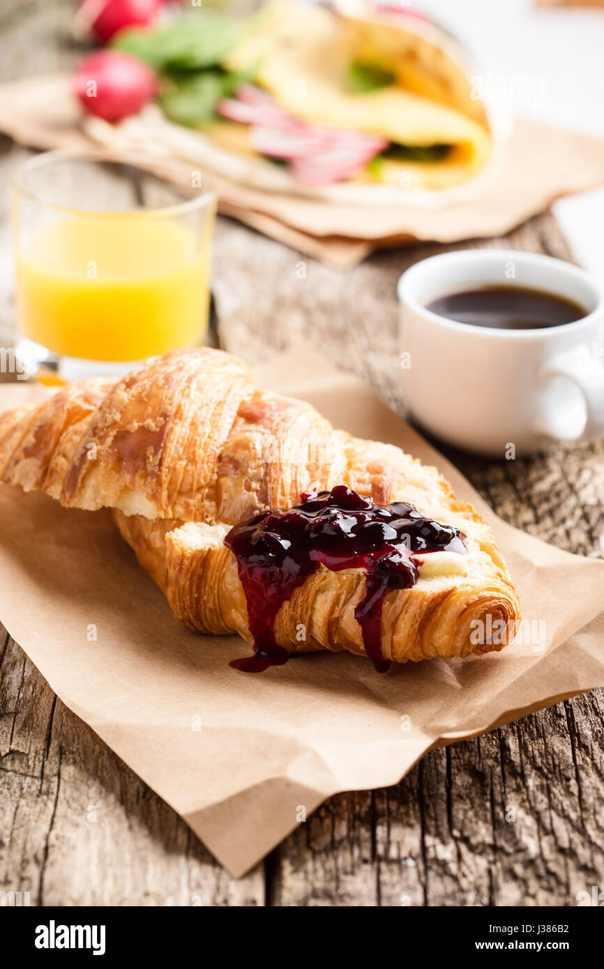 Croissant with jam and coffee cup on wooden board, brunch table - Stock Image