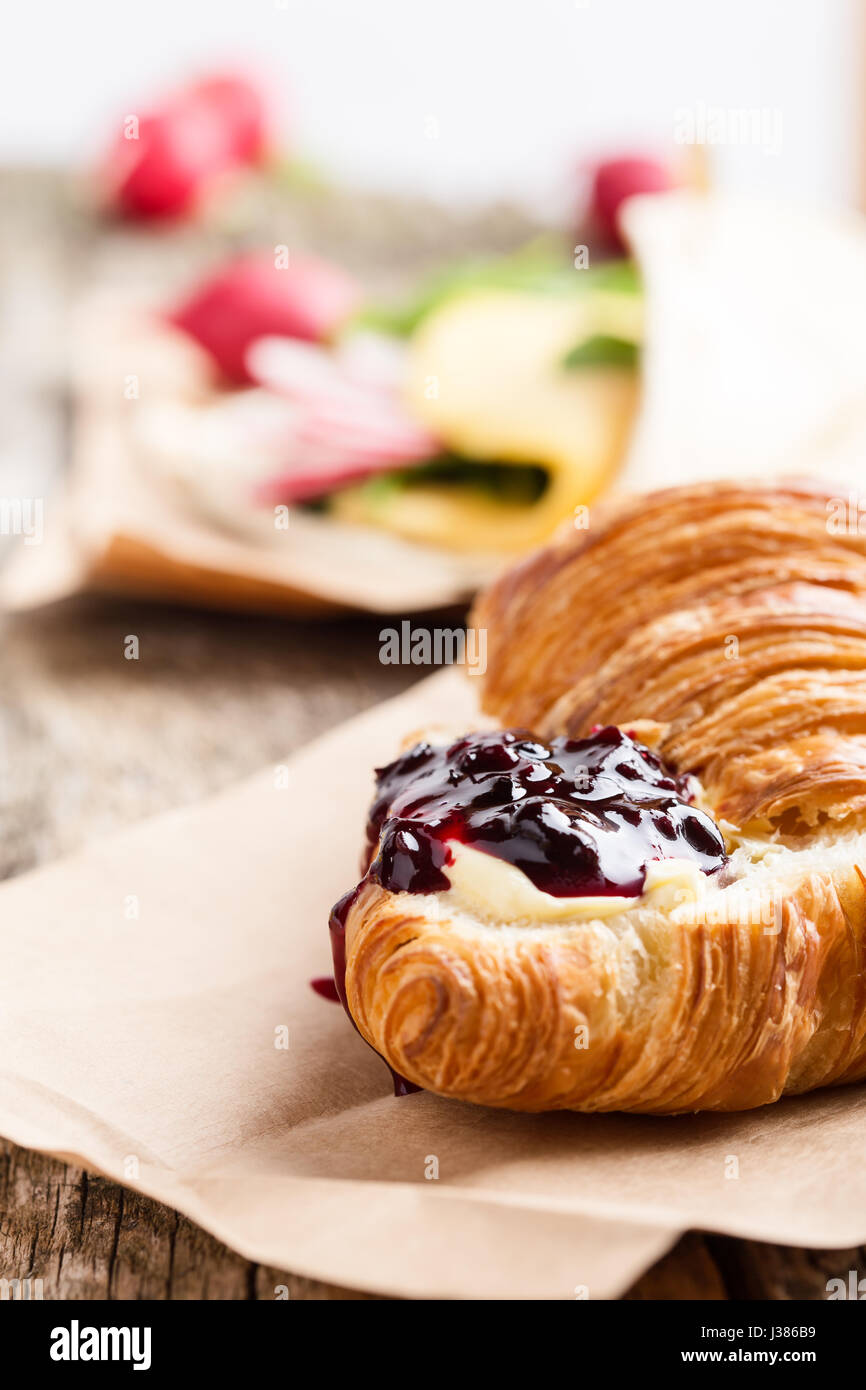 Croissant with jam on wooden board, brunch table - Stock Image