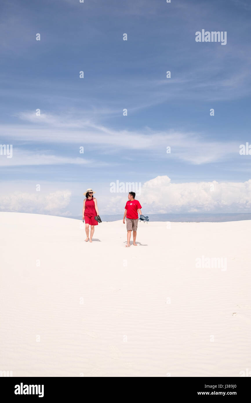 Mother and son in bright red dresses having fun at the White Sands National Monument, New Mexico, United States - Stock Image