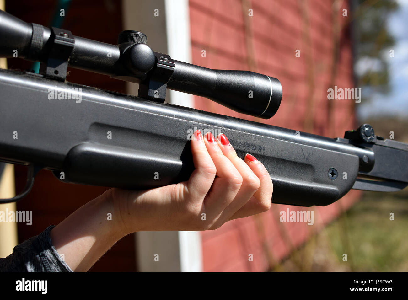 Woman holding and aiming with the air rifle. - Stock Image