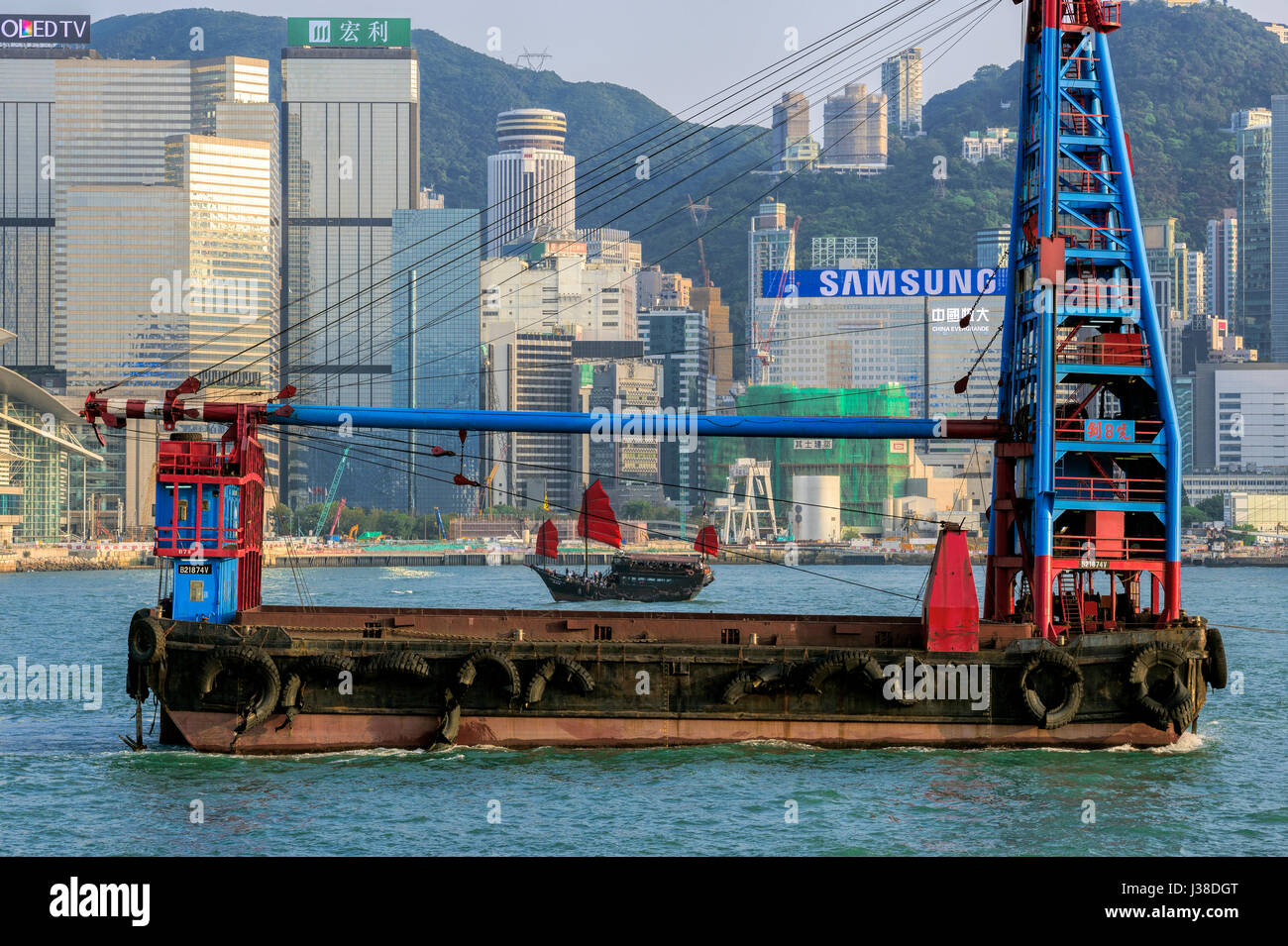 Traditional Chinese junk and floating crane boat, Victoria harbor, Hong Kong, China. - Stock Image