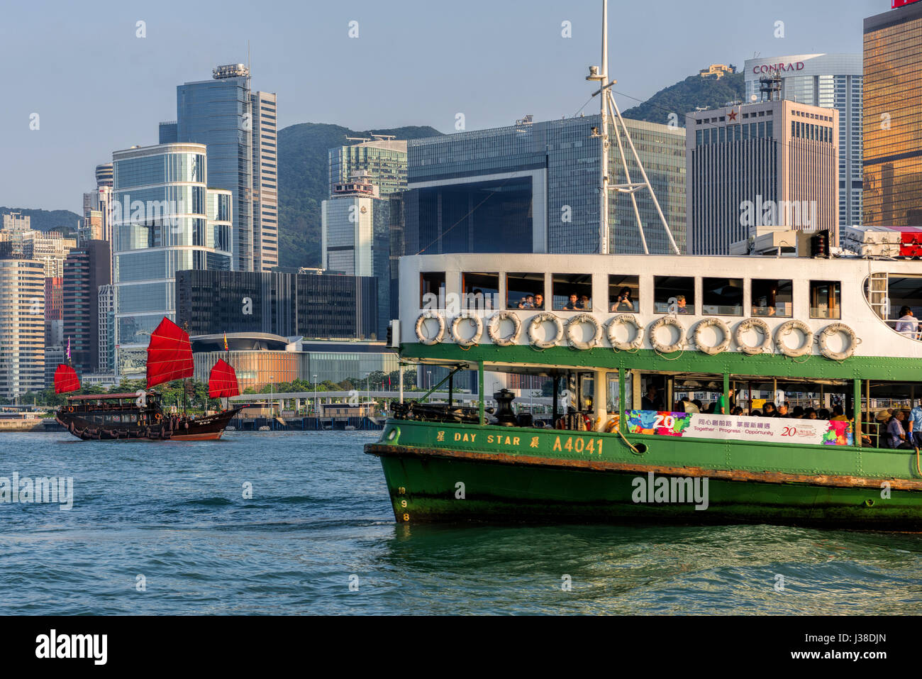 Traditional Chinese junk and Star ferry, with the Hong Kong financial district skyline, Victoria harbor, Hong Kong, - Stock Image