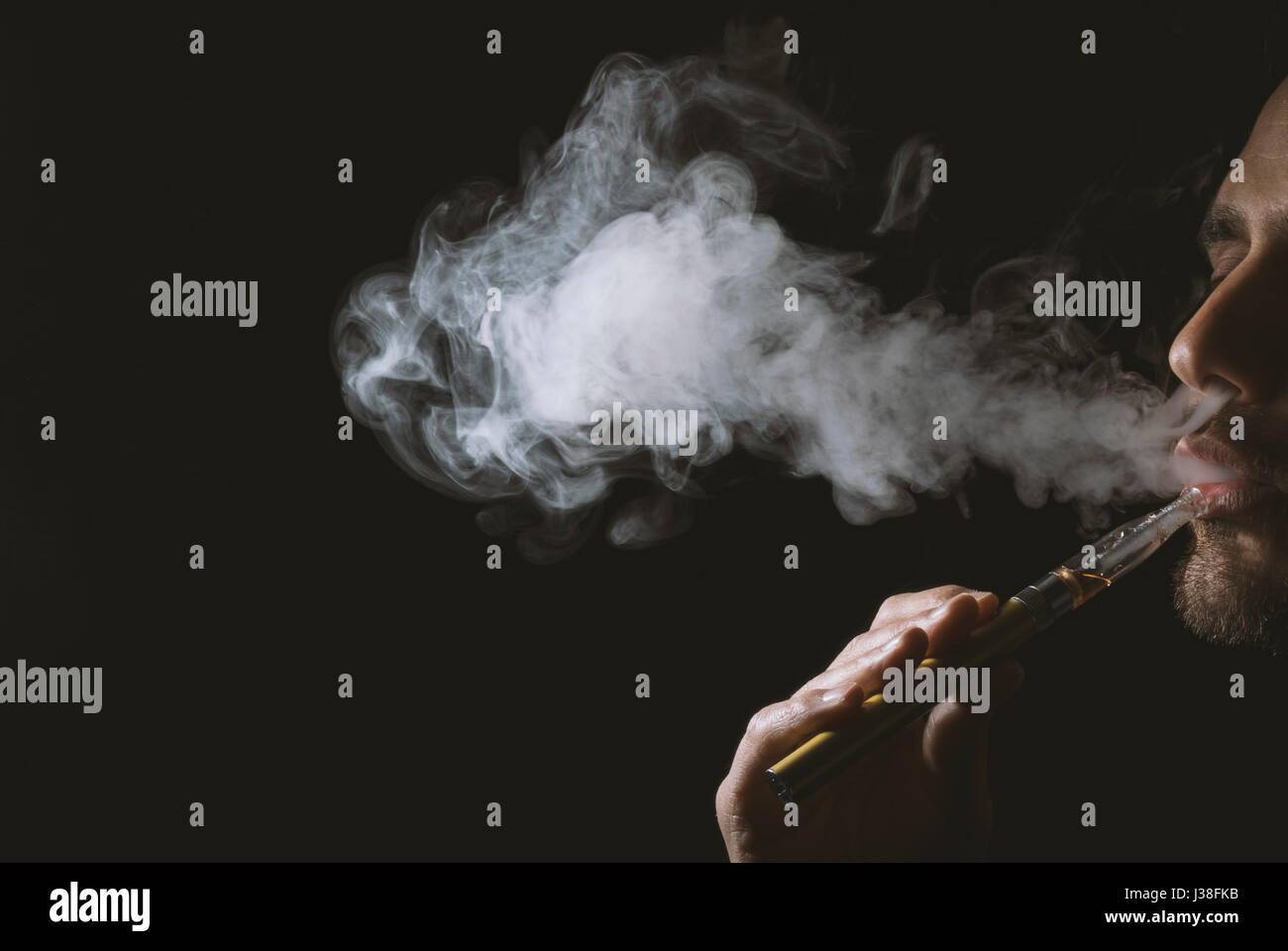Young man holding and vaping an electronic cigarette, e-cig, ecigarette. - Stock Image