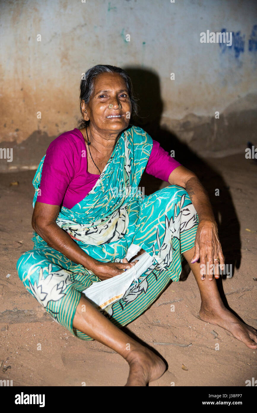 Documentary editorial image. Pondicherry, Tamil Nadu, India - April 24 2014. Very poor woman sitting in the street during the night. Poverty Stock Photo