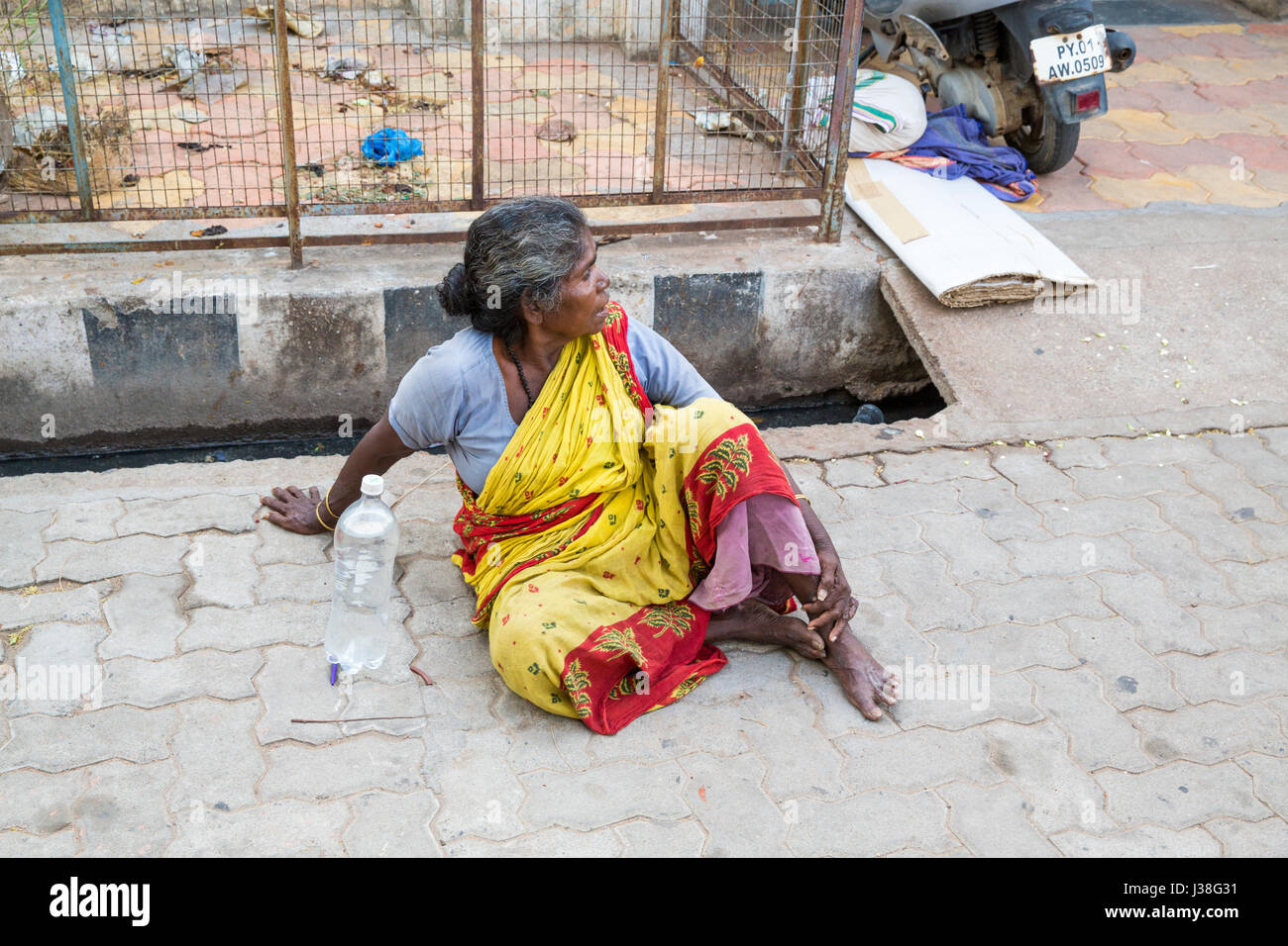 Documentary editorial image. Pondicherry, Tamil Nadu, India - June 23 2014. Very poor woman sitting in the street asking for food Poverty Stock Photo