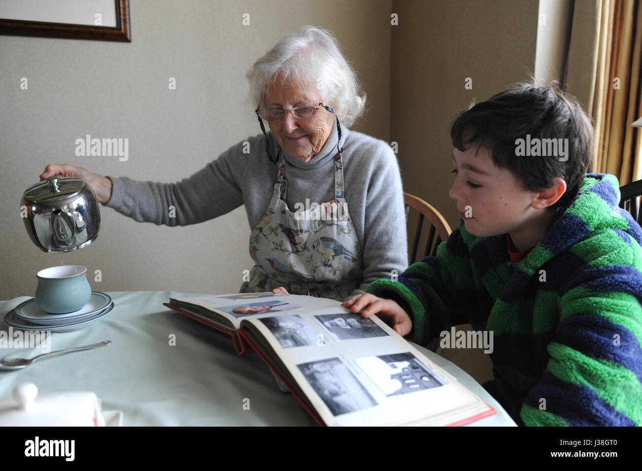 81 year old Grandmother and 12 year old grandchild looking at a photo album - Stock Image