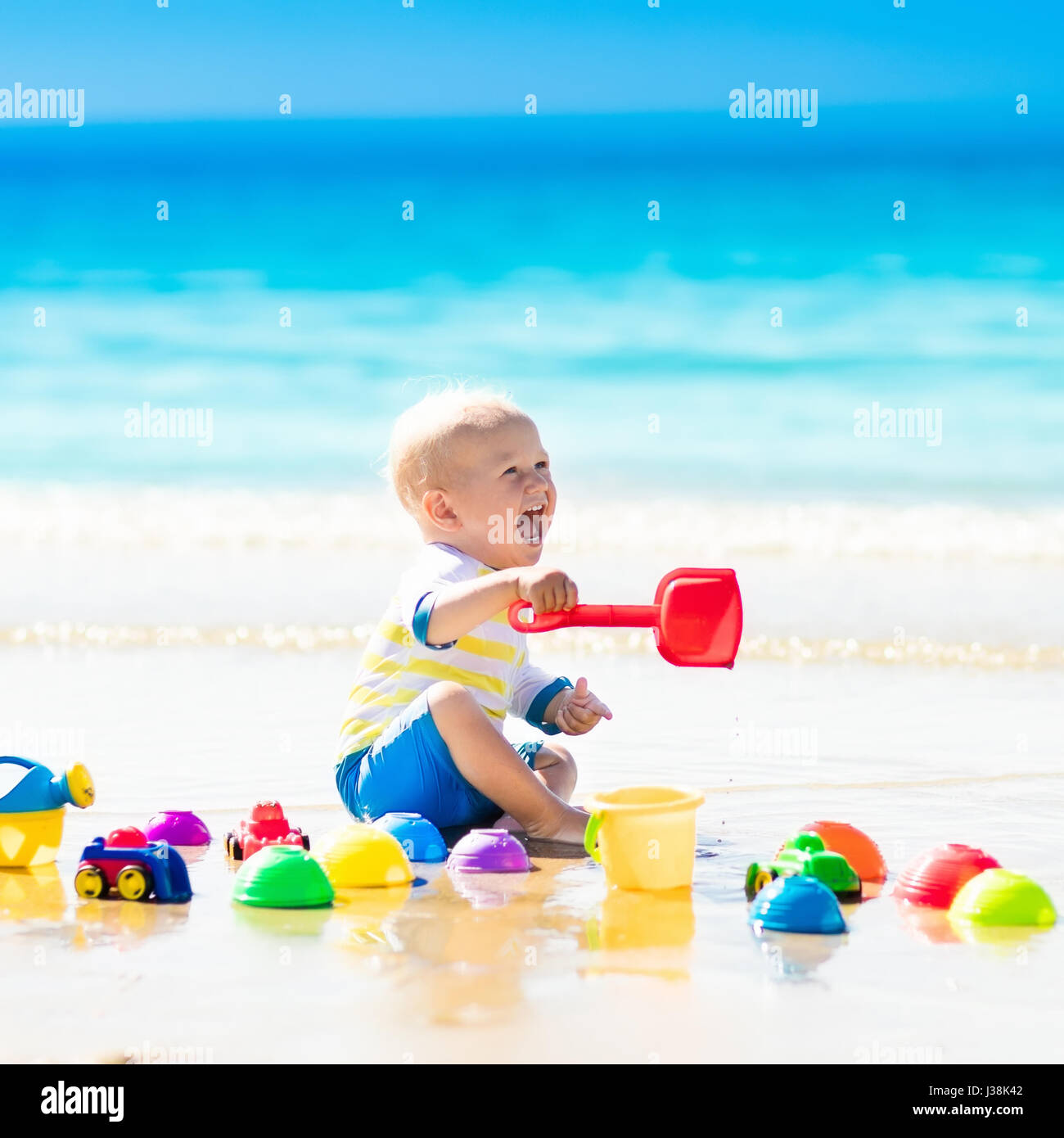Cute laughing baby boy wearing sun protection rash guard playing with bucket and shovel on tropical beach during - Stock Image