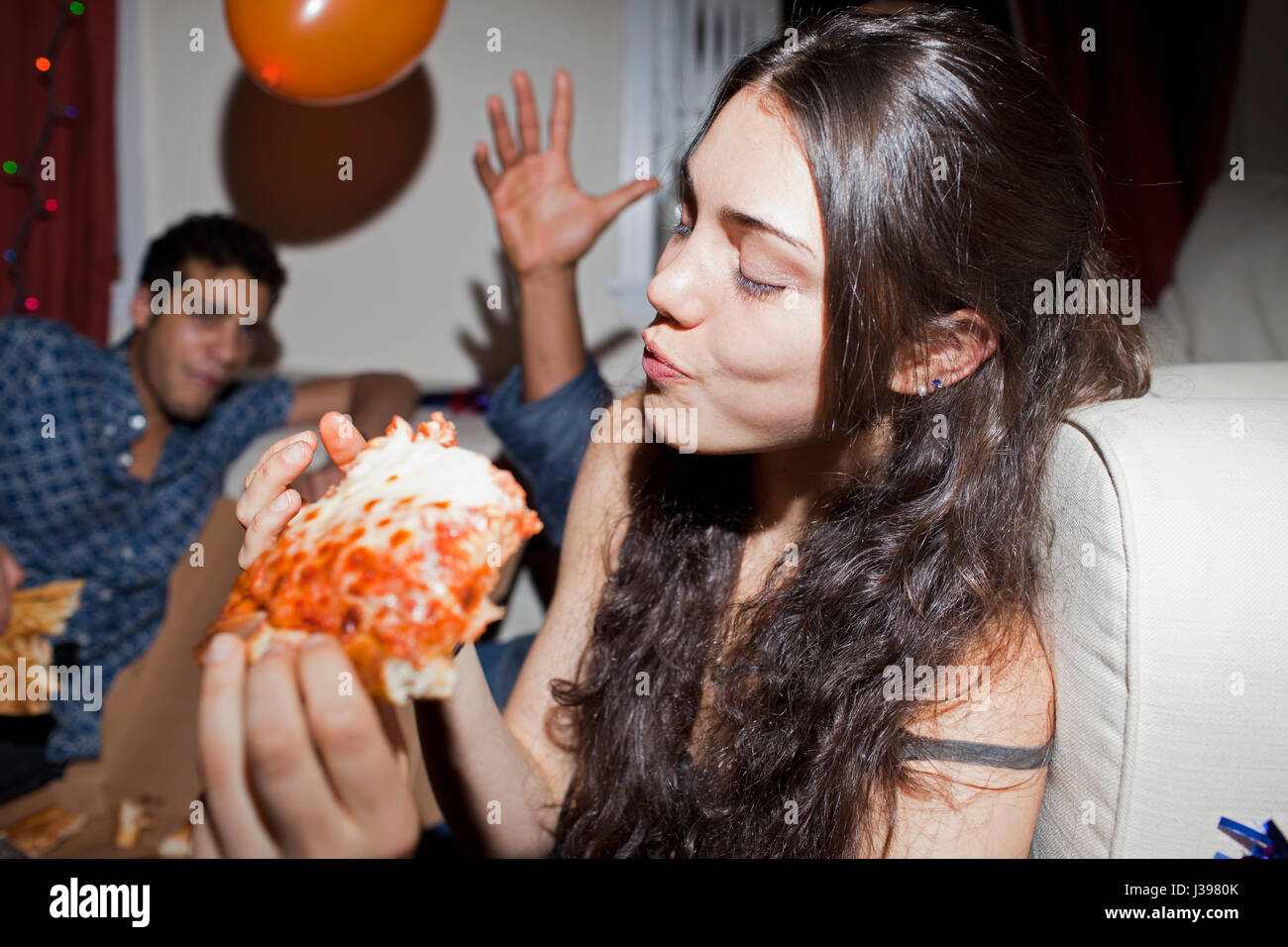 Young woman eating pizza - Stock Image