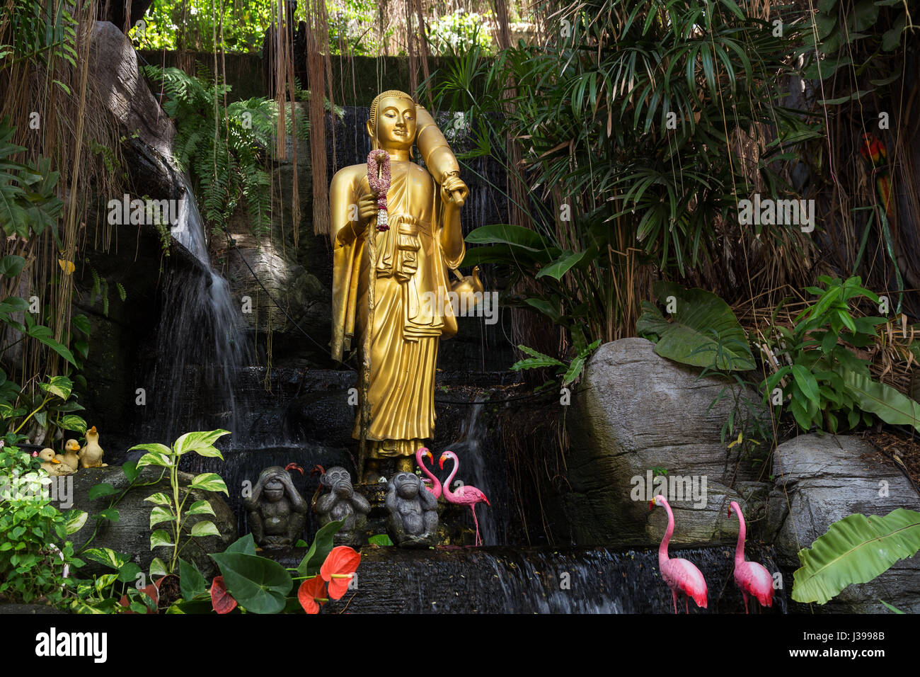 Golden Buddha statue and small artificial waterfall at the Golden Mount at Wat Saket in Bangkok, Thailand. - Stock Image