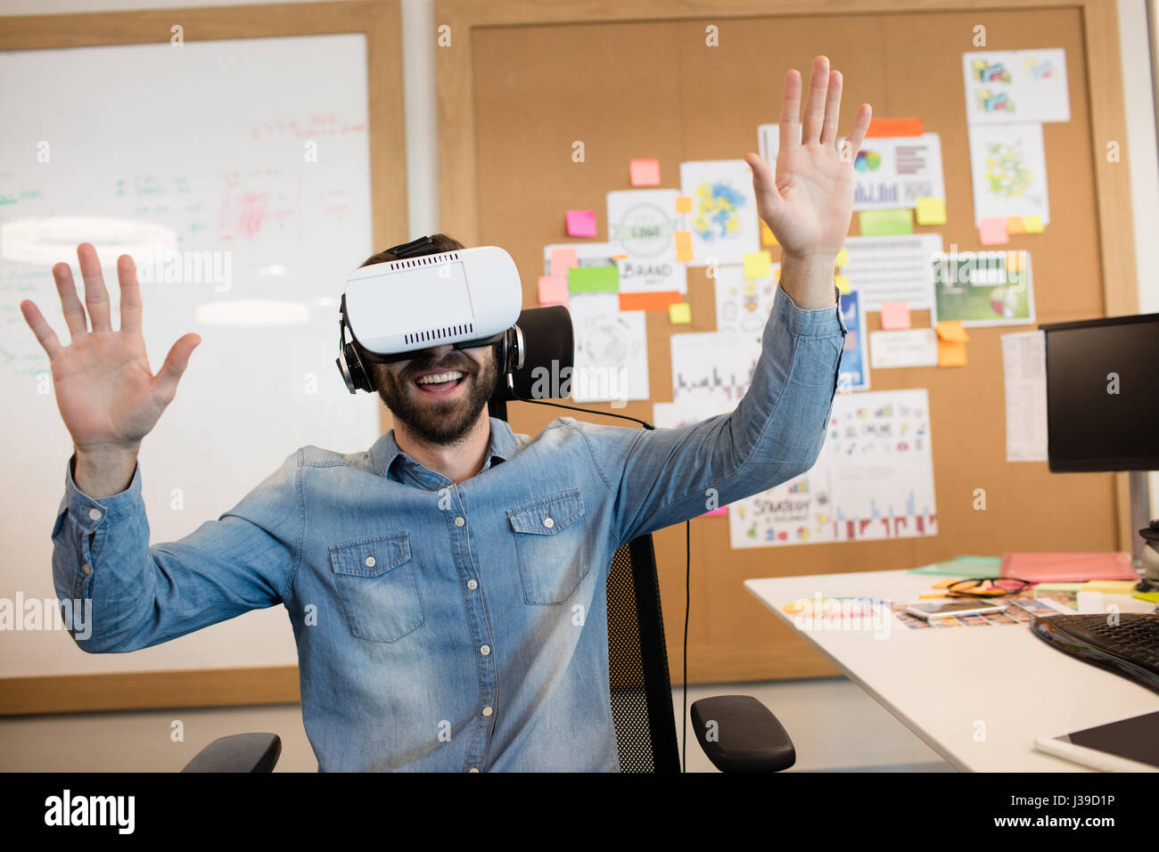 Businessman experiencing virtual reality in modern office - Stock Image