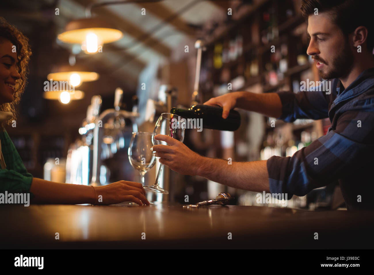 Male bar tender pouring wine in glasses at bar counter - Stock Image