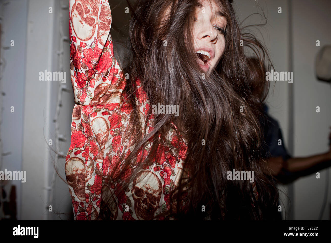 Young woman dancing at a party - Stock Image