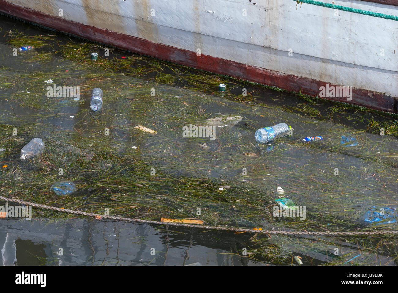 Concept of polution : Fishing boats on the dirty beach full of plastic trashes - Stock Image