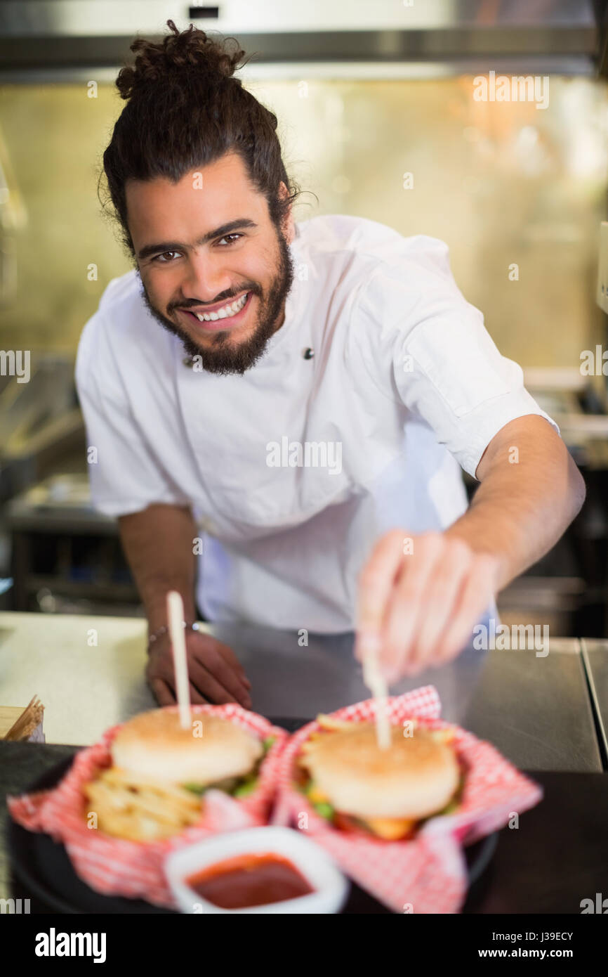 Portrait of happy male chef preparing burger in commercial kitchen - Stock Image