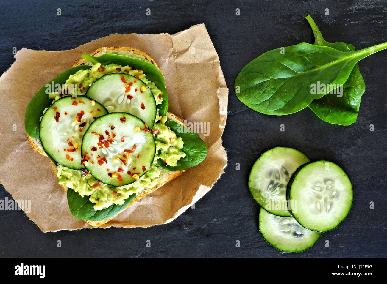 Avocado toast with cucumber, spinach and whole grain bread on paper against a dark slate background - Stock Image