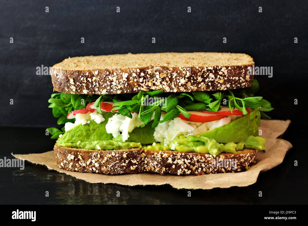 Superfood sandwich with avocado, egg whites, radish and pea shoots on whole grain bread against a slate background - Stock Image