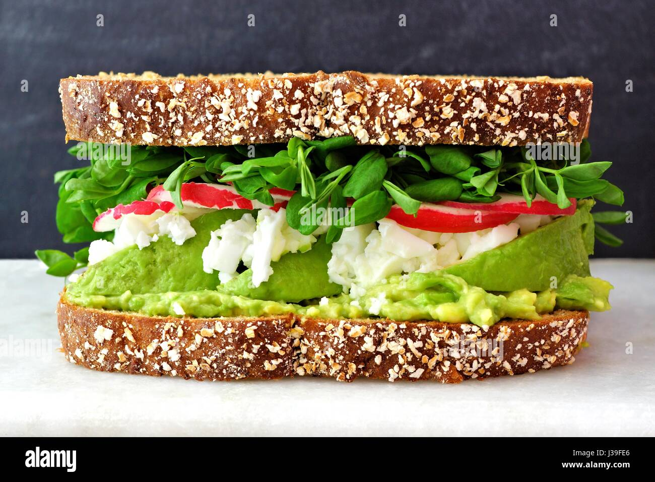 Superfood sandwich with whole grain bread, avocado, egg whites, radishes and pea shoots on marble against a black - Stock Image